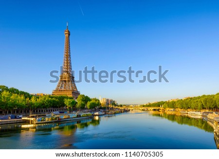 View of Eiffel Tower and river Seine at sunrise in Paris, France. Eiffel Tower is one of the most iconic landmarks of Paris. Architecture and landmarks of Paris. Postcard of Paris #1140705305