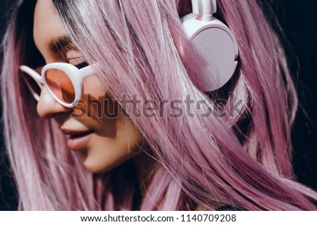 Beautiful young girl with purple pink hair listening to music on headphones, street style, outdoor portrait, hipster girl, music, mp3, Bali, beauty woman, sunglasses, orange color, concept #1140709208