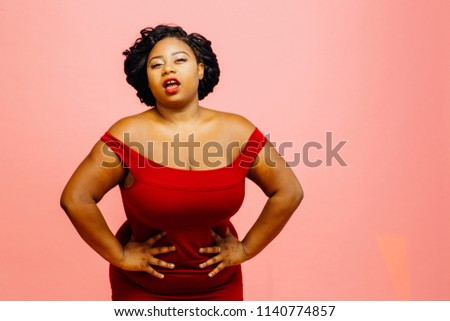 Confident curvy woman in red dress with hands on waist, mouth open, isolated on pink  #1140774857