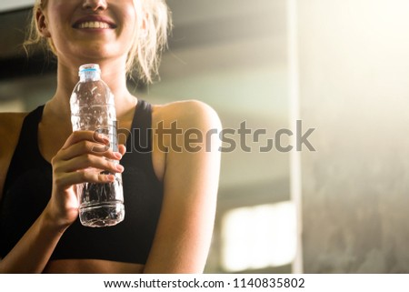 Young beautiful woman drinking water after training at the gym. #1140835802
