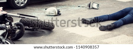 Fatal aftermath of a car accident concept - dead body and crashed motorcycle parts lying on the road #1140908357