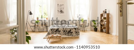Glass door entrance into a beautiful, bright bedroom interior with breakfast tray on a wooden floor and black floral pattern sheets on a comfy bed