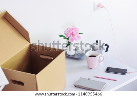 table with stationery, unpacking box with books. girl Back to college. Coffee, flowers, notebook #1140955466