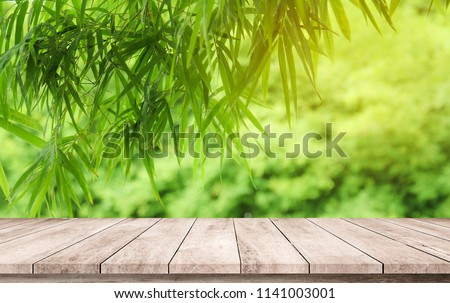Wood plank with abstract natural blurred bamboo forest and bokeh background for product display