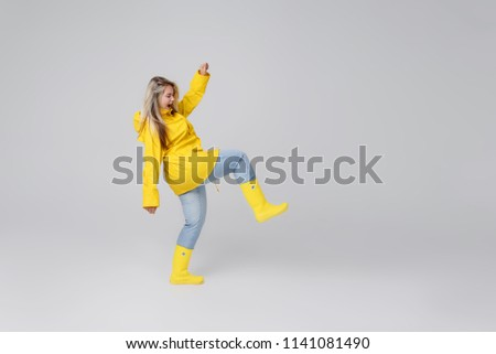 Young woman blonde in a yellow raincoat and yellow rubber knee-boots on a white background. Gladly steps after a rain and jumps over through puddles  #1141081490