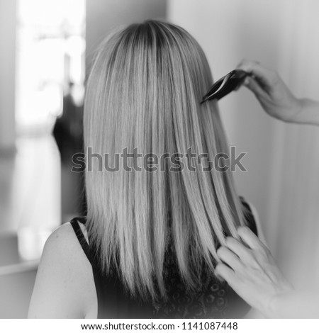 Black and white photo in the beauty salon. Hairdresser combs beautiful hair. Blurred background #1141087448