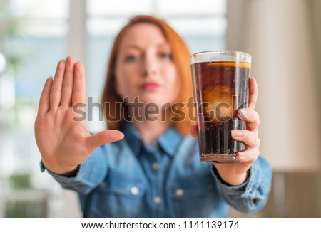 Redhead woman holding soda refreshment with open hand doing stop sign with serious and confident expression, defense gesture #1141139174