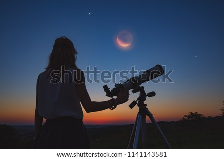 Girl looking at lunar eclipse through a telescope. My astronomy work. Royalty-Free Stock Photo #1141143581