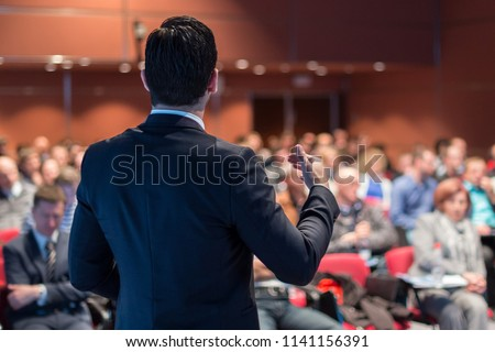 Speaker giving a talk on corporate business conference. Unrecognizable people in audience at conference hall. Business and Entrepreneurship event. #1141156391