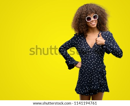 African american woman with sunglasses and summer dress happy with big smile doing ok sign, thumb up with fingers, excellent sign #1141194761