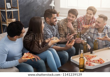 Young people in casual clothes eating pizza, talking and drinking beer at home #1141239539