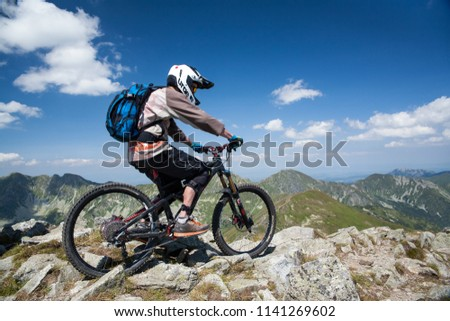 Baraniec / Slovakia - July 22, 2018: Mountain bike on top of the mountain. Downhill on a bike from a steep slope. Bicycle extreme sport. Sporting activity in the mountains. #1141269602