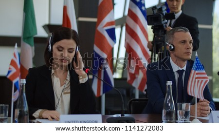 Formal international politicians in headphones sitting at table on summit and listening to speech translation in headphones