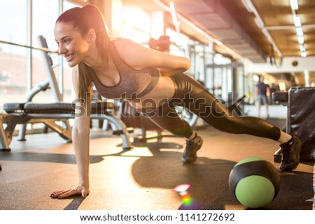 Athletic young sportswoman doing one hand push-ups in the gym #1141272692
