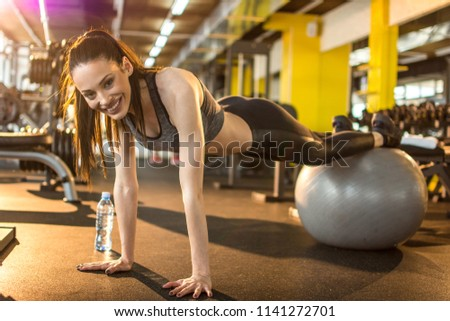 Young sporty woman exercising on pilates ball in gym #1141272701