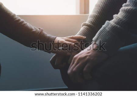 PTSD Mental health concept, Psychologist sitting and touch hand young depressed asian man for encouragement near window with low light environment.Selective focus. #1141336202