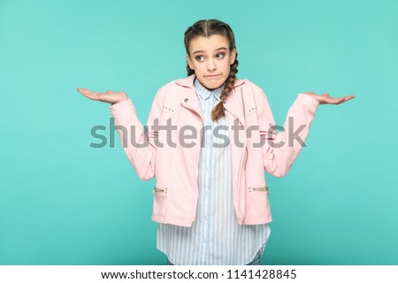 i dont know, thinkful portrait of beautiful cute girl standing with makeup and brown pigtail hairstyle in striped light blue shirt pink jacket. indoor, studio shot isolated on blue or green background #1141428845