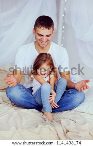 Happy father and daughter having fun at home. Cute smiling little girl with her handsome dad paints  #1141436174