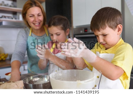 Mother and children together making apple pie in the kitchen at home. Children helping mother. Kitchen Activities for Children #1141439195