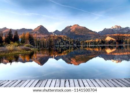 Mountain lake in the autumn season. Beautiful lake in Slovakia - Strbske Pleso. Saturated autumn colors. #1141500704
