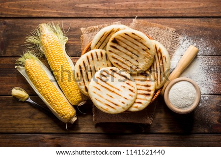View from above of wooden rustic table with several ground corn Arepas, some corn and butter. Venezuelan traditional cuisine #1141521440