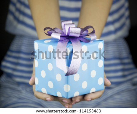 girl holding present box with ribbon bow