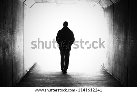 Black and white shot of a male person figure in a tunnel heading towards a bright light. Concept of near death experience, dying, afterlife, moving on, transition, heaven. walking towards the light.  #1141612241