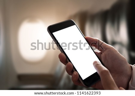 Mockup image of a hand holding a smart phone with blank desktop screen on airplane window, Blank screen mobile phone for graphic display montage #1141622393