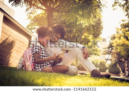 African American father with daughter sitting on grass and using digital tablet. #1141662152