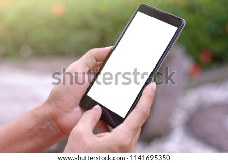 Woman hands holding and using black mobile smartphone with blank white screen isolated on  blurred background.clipping path. #1141695350
