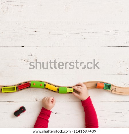 Top view on toy wooden trains on railway on white wooden table background. Child's hands playing with educational toys. #1141697489