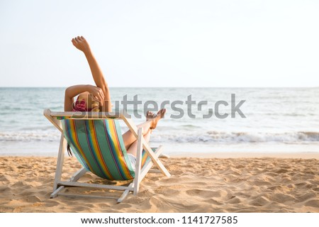 Summer beach vacation concept, Asia woman with hat relaxing and making heart sign on chair beach at Koh Mak, Trad, Thailand #1141727585