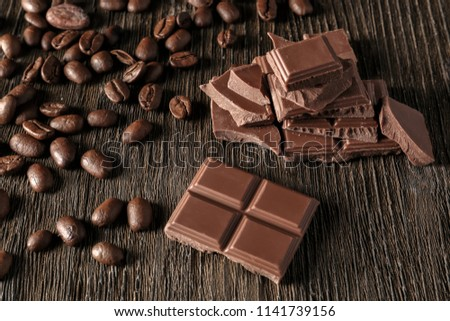 Pieces of tasty milk chocolate and coffee beans on wooden background #1141739156