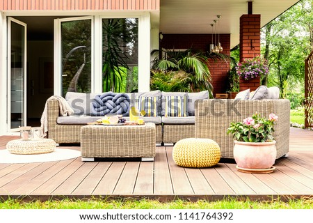 Garden table with fruits and fresh orange juice standing on wooden terrace with plants, armchair and sofa with pillows #1141764392