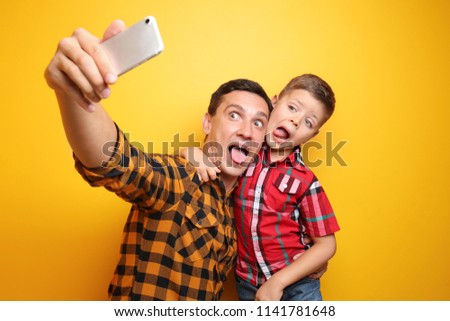 Little boy and his dad taking funny selfie on color background #1141781648