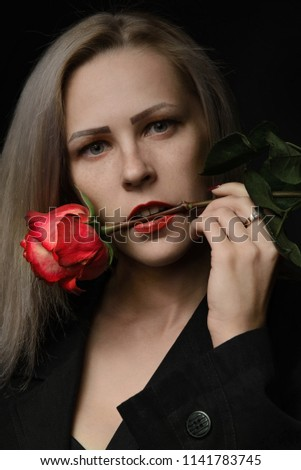 Beautiful young blonde woman with freckles holding a red rose in her mouth isolated on dark backround. #1141783745