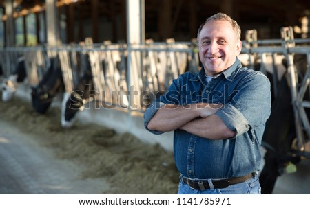 Portrait of man who is standing near cows at the farm. #1141785971