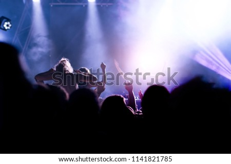 Silhouettes of concert crowd in front of bright stage lights #1141821785