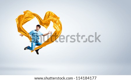Young man dancing with yellow fabric over white background #114184177