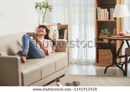 Pretty Vietnamese woman lying of sofa and laughing when watching funny videos #1141915928