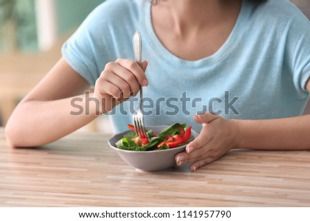 Young woman eating healthy salad with vegetables at home #1141957790
