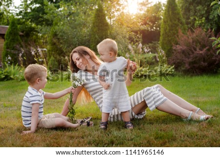 Mom, two children rest on nature. Sibling rivalry. Brothers, the son gives his mother flowers. Motherhood. #1141965146