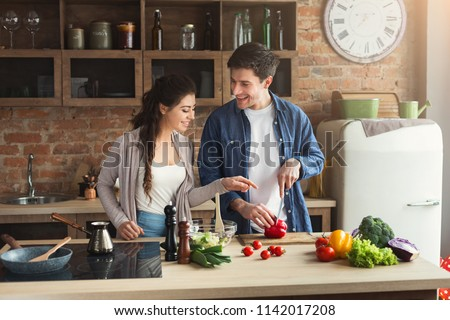 Happy couple cooking dinner together in their loft kitchen at home. Man preparing vegetable salad for his girlfriend, copy space Royalty-Free Stock Photo #1142017208