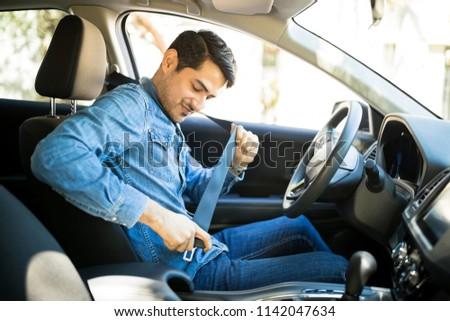 Young latin man sitting on car seat fastening seat belt Royalty-Free Stock Photo #1142047634