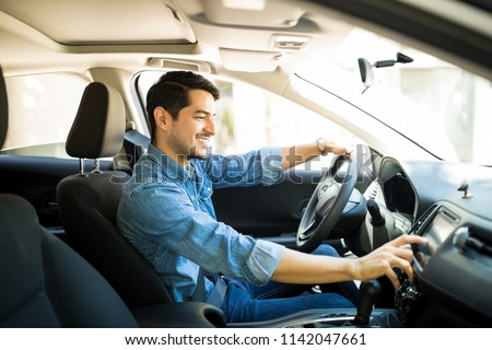 Handsome young man in denim shirt pressing touchscreen on car multimedia panel, switching shifting radio station. #1142047661
