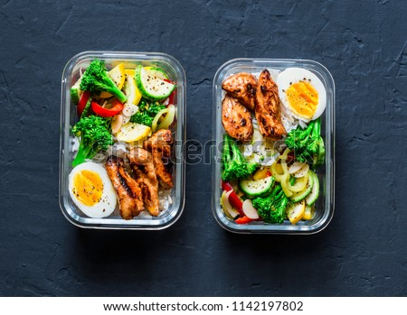 Rice, stewed vegetables, egg, teriyaki chicken - healthy balanced lunch box on a dark background, top view. Home food for office concept #1142197802