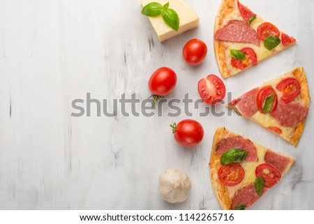 Delicious sliced pizza with tomatoes, mozzarella cheese, basil, and a tomato on a light background,Copyspace. Top view. #1142265716
