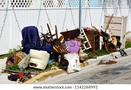 A pile of household furnishings, damaged by Hurricane Irma, placed curbside, awaiting trash removal. #1142268992