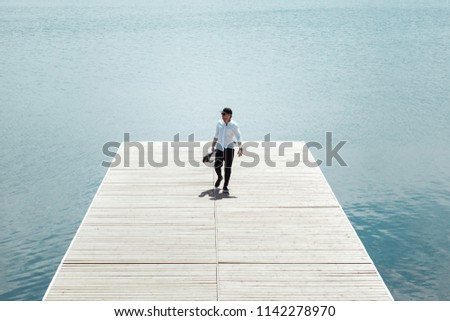 Photo of modern man with electric scooter at a wooden pier #1142278970