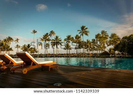 Beautiful tropical beach front hotel resort with swimming pool, sun-loungers and palm trees during a warm sunny day, paradise destination for vacations in Praia do forte, Bahia, Brazil. Royalty-Free Stock Photo #1142339339